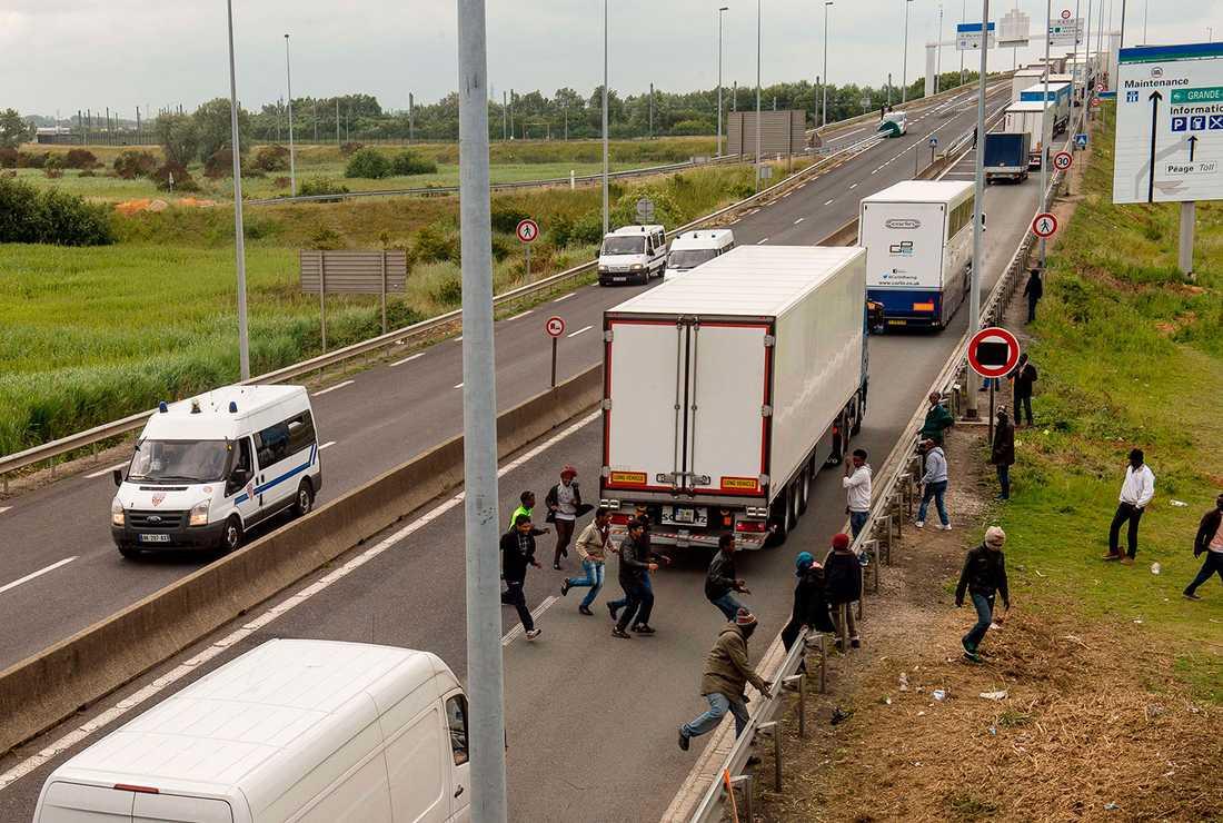 Emigranter försöker ta sig ombord på lastbilarna i den långa kön.