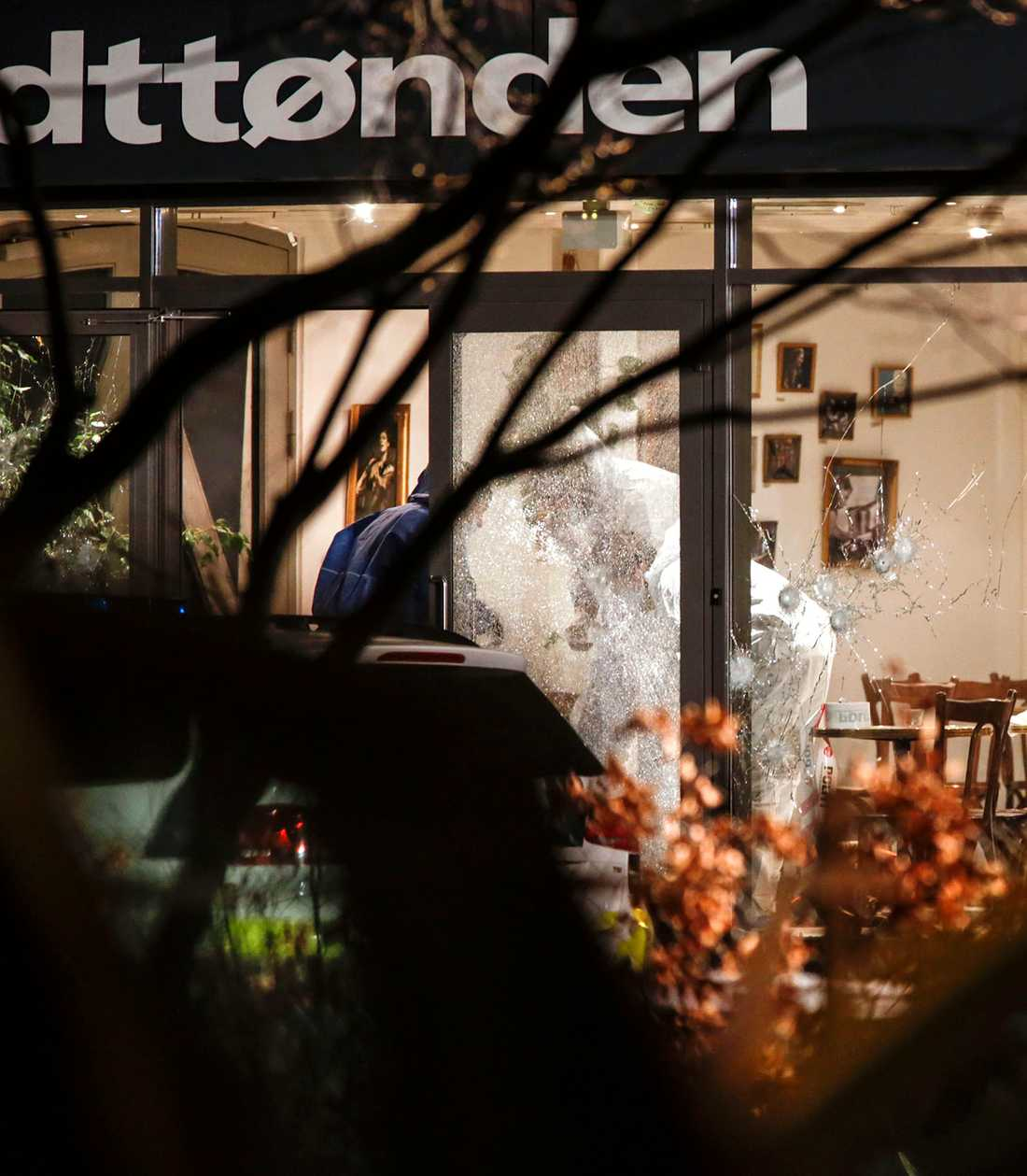 Polisens tekniker undersöker den sönderskjutna entrén till kulturhuset Krudttønden i stadsdelen Østerbro i Köpenhamn där konstnären Lars Vilks deltog i ett debattmöte.