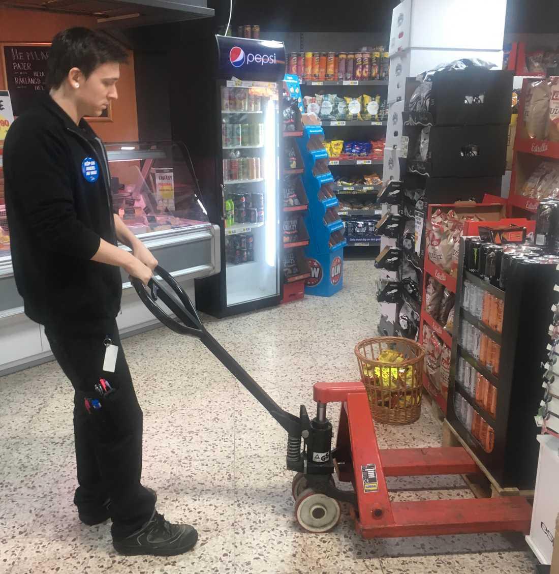 Butikschefen Christoffer Svensson rensar bort energidryck från butiken.