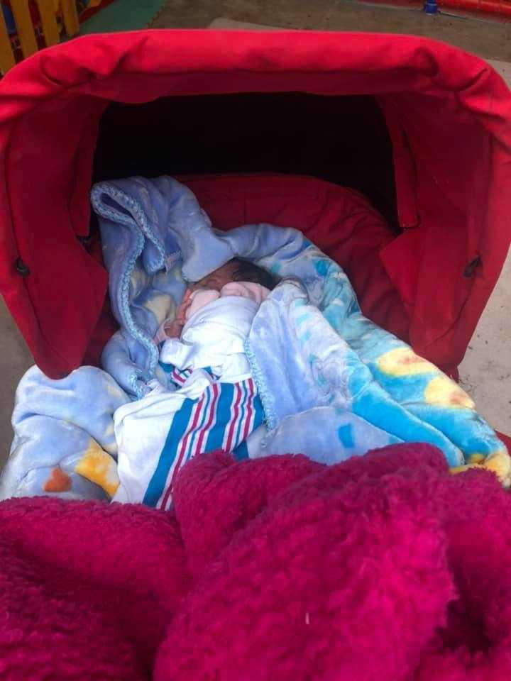 Små barn får sova på blöta filtar på marken i lägret. En barnvagn ger en varm sovplats.