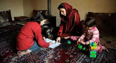 Mamma Souheila, 28, hjälper dottern Maria med läxorna.
