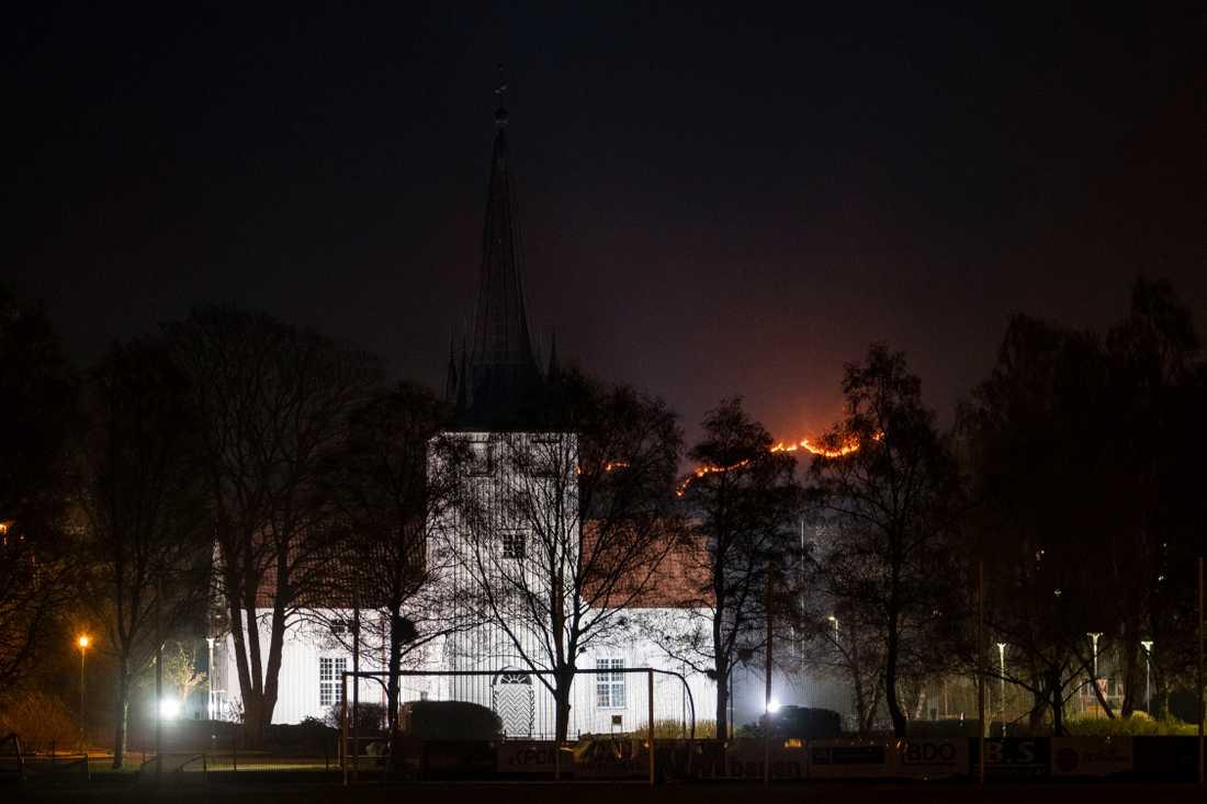 Det brinner i Sokndal kommun i Norge. På bilden Sokndals kyrka med lågorna i bakgrunden.