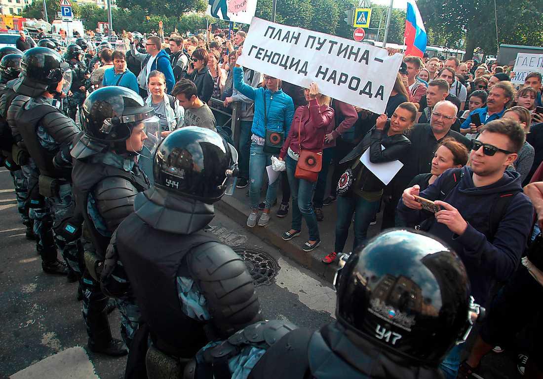 """Rysk kravallpolis stoppar demonstranter med banderollen """"Putins plan är folkmord"""" i samband med demonstrationer mot den nya pensionsreformen  i Sankt Petersburg den 9 september."""