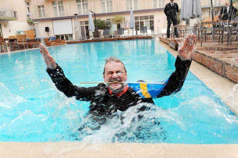 Christer Björkman tar ett dopp i poolen – med kläderna på.
