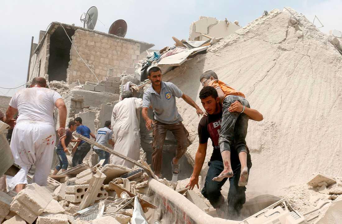 En pojke räddas ut bråten efter regimens bombardemang.