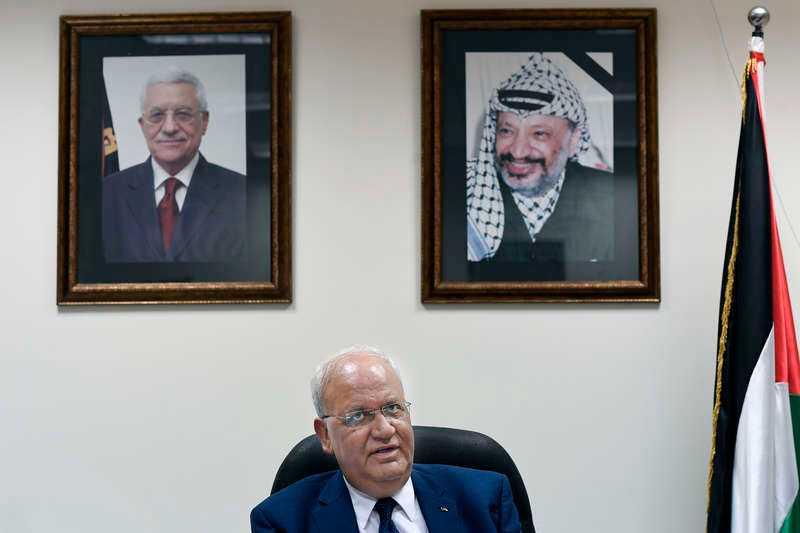 Chefsförhandlare Saeb Erekat på sitt kontor.  Bakom sig har han porträtt av palestiniernas president Mahmoud Abbas och den förre ledaren Yassir Arafat