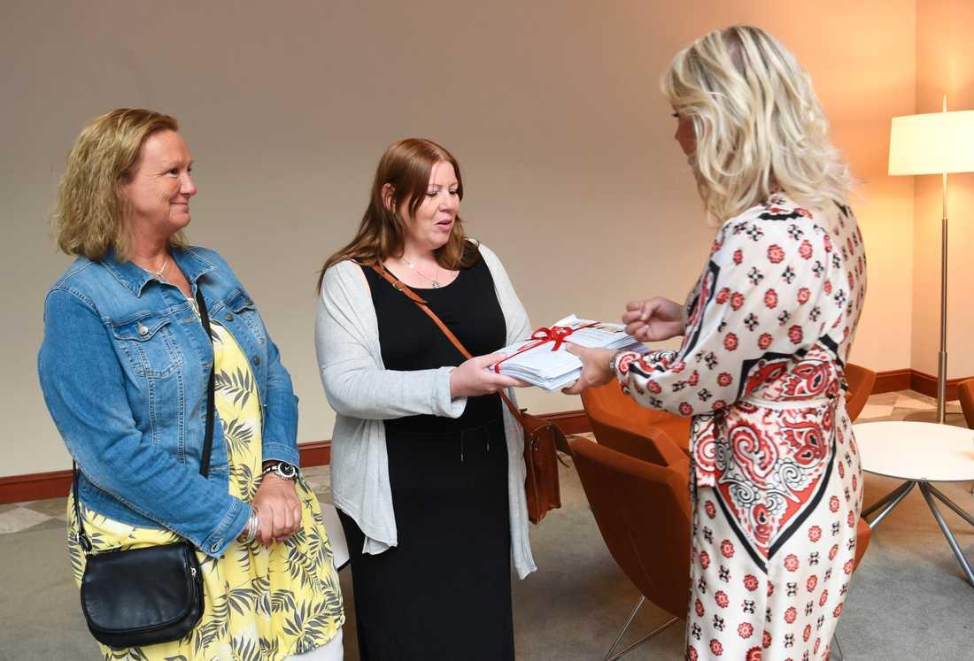 Undersköterskorna Jenny Klingstam och Mari Viberg lämnar över namninsamlingen från undersköterskeuppropet till soclailminister Lena Hallengren (S) på Socialdepardementet i Stockholm.