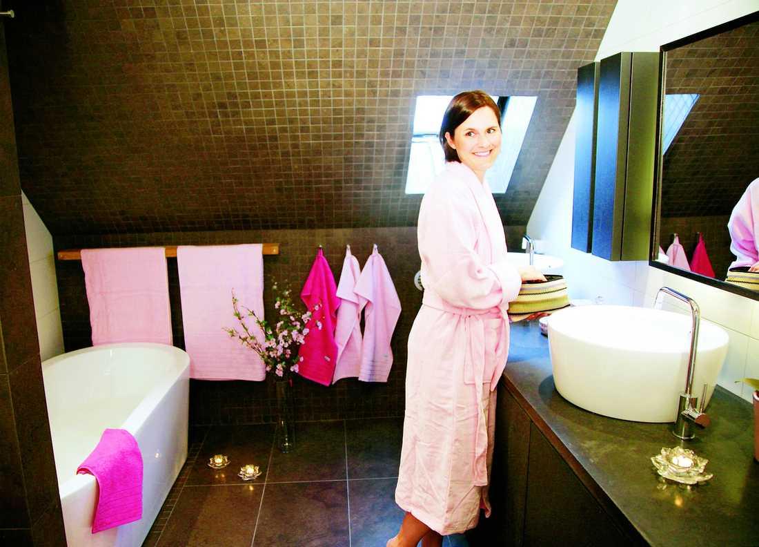 Rymd och ljus i skön harmoni med det varmt bruna i väggar och golv. Sara älskar att bada och njuter av sitt nyrenoverade badrum. Alla textilier kommer från Hemtex.
