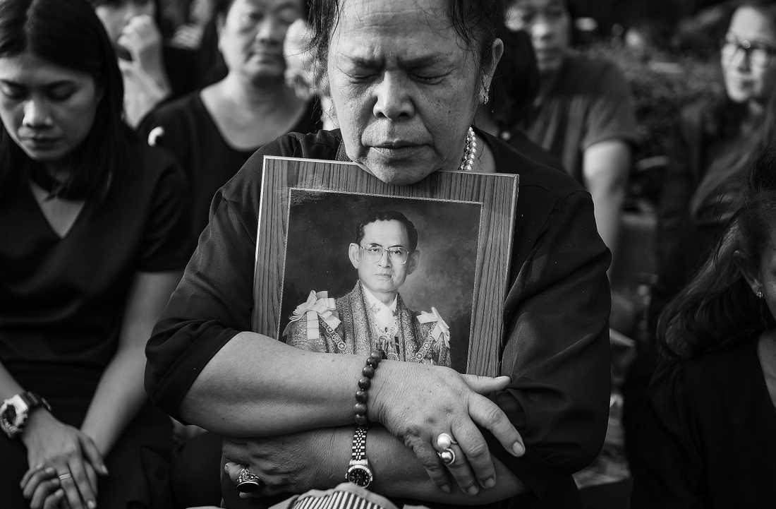 En kvinna kramar om en bild av avlidne kung Bhumibol Adulyadej.