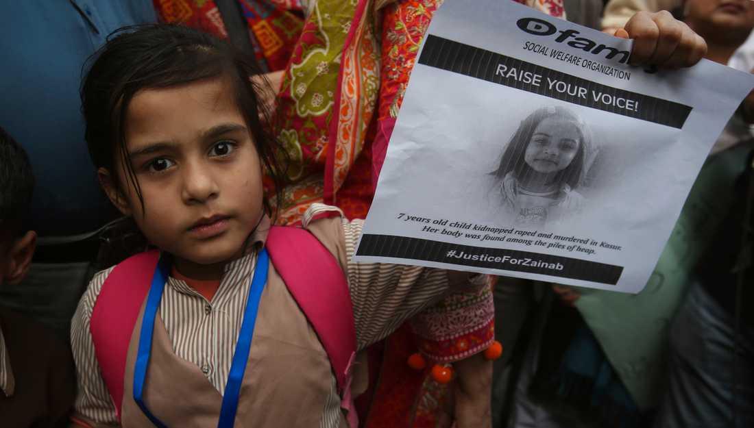 En flicka håller upp ett porträtt av den mördade Zainab Ansari.