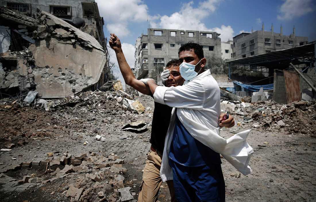 En sjukvårdare hjälper en chockad man i Gaza.