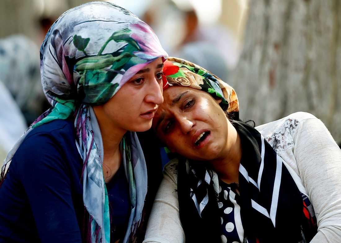 Två kvinnor väntar på besked om sina anhöriga utanför sjukhuset.