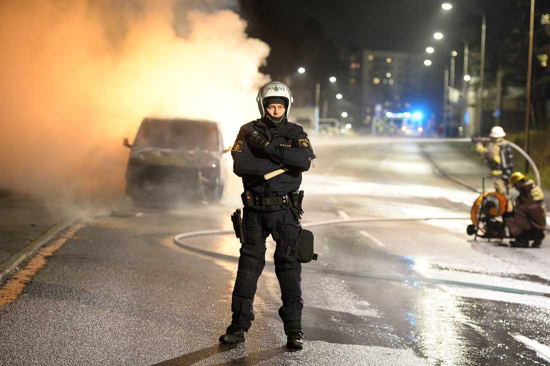 En polis vaktar medan brandmännen släcker en bildbrand.