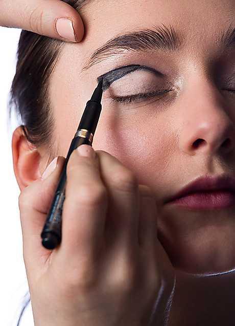 3. När du är nöjd med formen fyller du i med en flytande eyeliner. Börja utifrån och gå mot mitten.