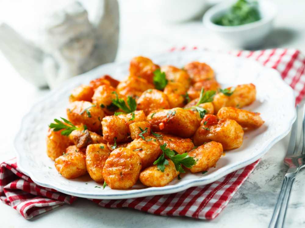 Servera gnocchin med krämig tomatsås.