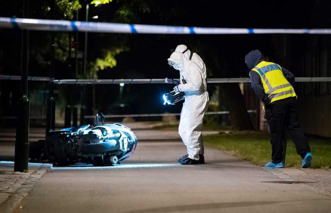 Polisens kriminaltekniker undersöker en moped vid Lindängsplan i Malmö efter att en man skjutits.