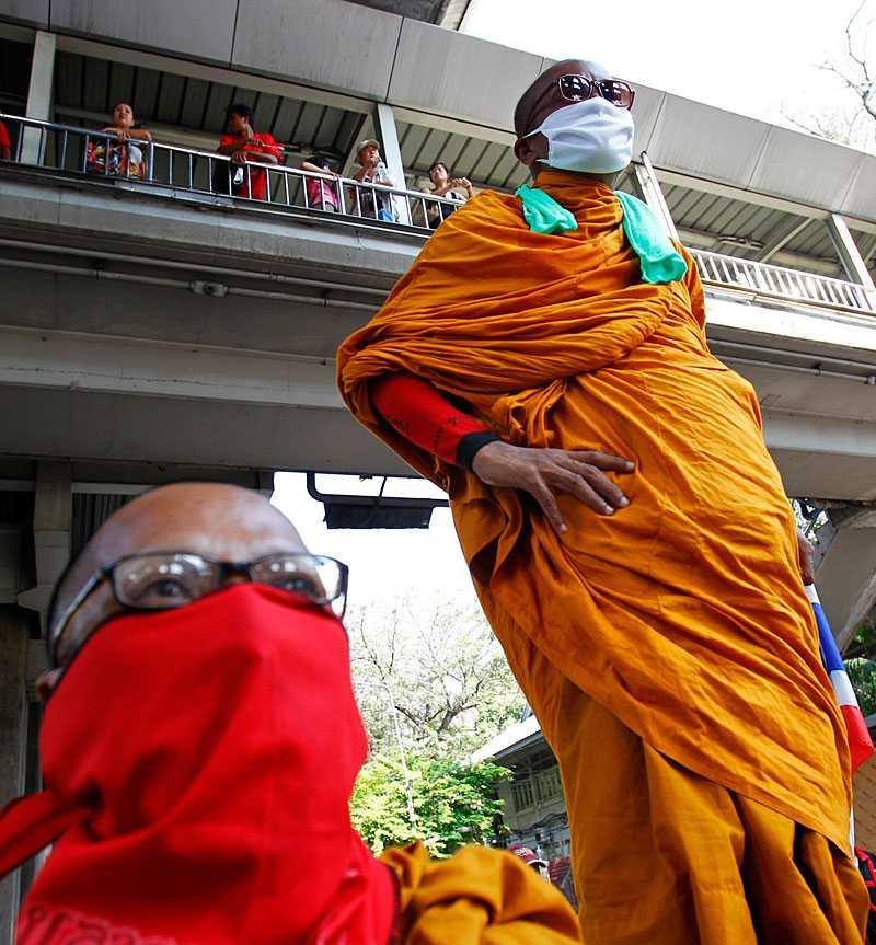 Maskerade munkar ger stillsamt sitt stöd till rödskjortorna nära shoppingcentret Rachaprasong i Bangkok.