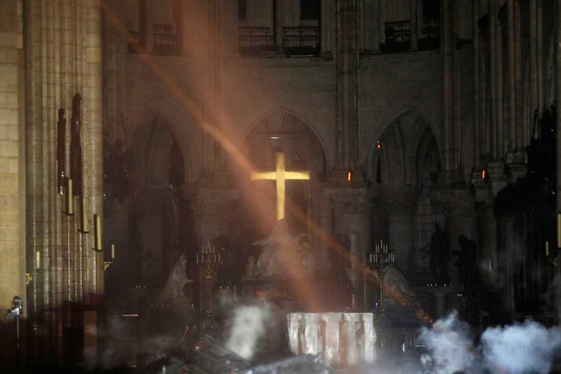 En av de första bilderna inifrån katedralen Notre-Dame efter branden. Rök syns framför altaret.