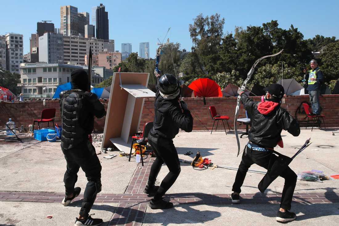 Demonstranter förbereder sig för att skjuta med pilbåge under en konfrontation med polisen vid polytekniska universitetet på söndagen.