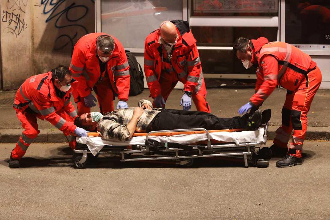 En medvetslös man som kollapsat på gatan, tas om hand av ambulanspersonal i Rom.