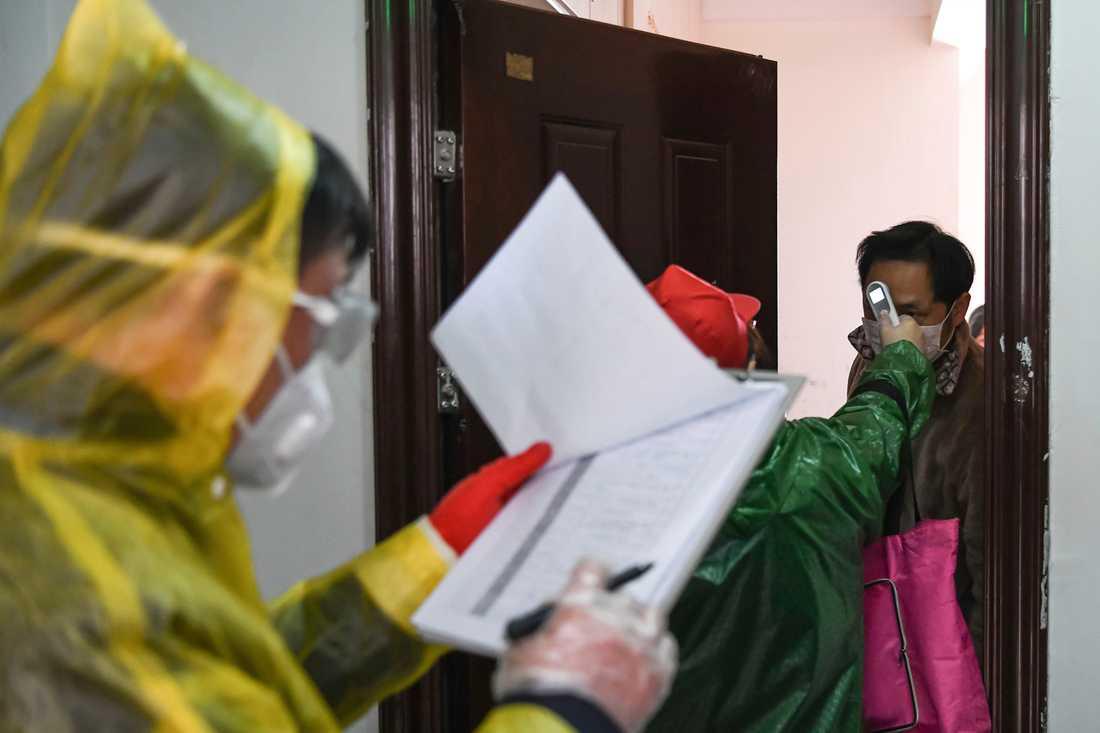 Invånare i Wuhan kontrolleras för feber i en dörrknackningskampanj. Bild från tidigare i veckan.
