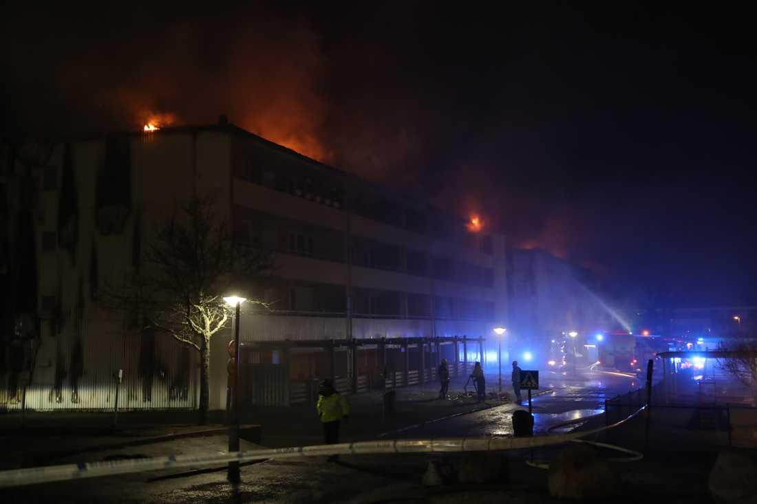 En kraftig brand rasar sedan tisdagskvällen i ett flerfamiljhus i Skövde. Boende i mellan 90 och 100 lägenheter har evakuerats.