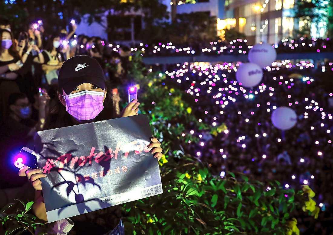 Demonstranter med mobiltelefoner lyser upp Hongkong. Protesterna har infiltrerats av lokal maffia som mutas av Kina.