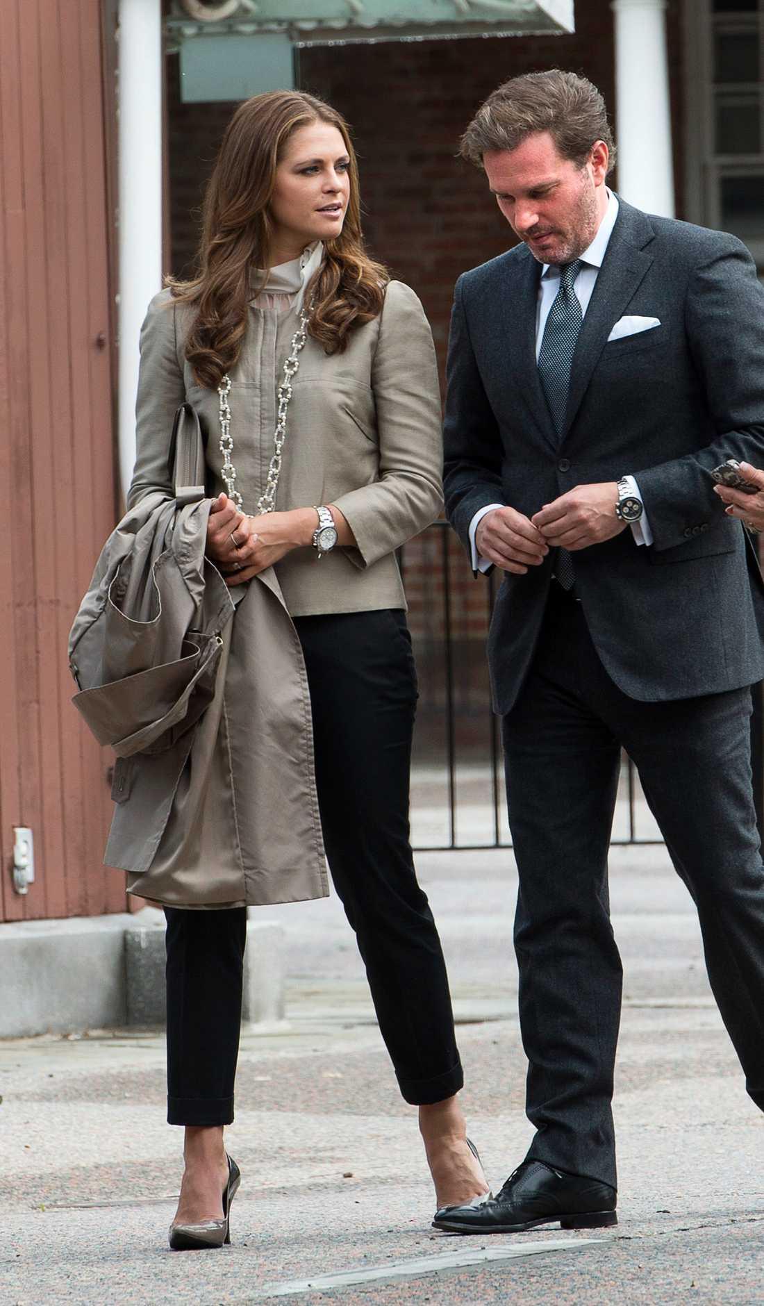 Madde är elegant i svarta byxor, proper jacka matchat med pumps och stort smycke.