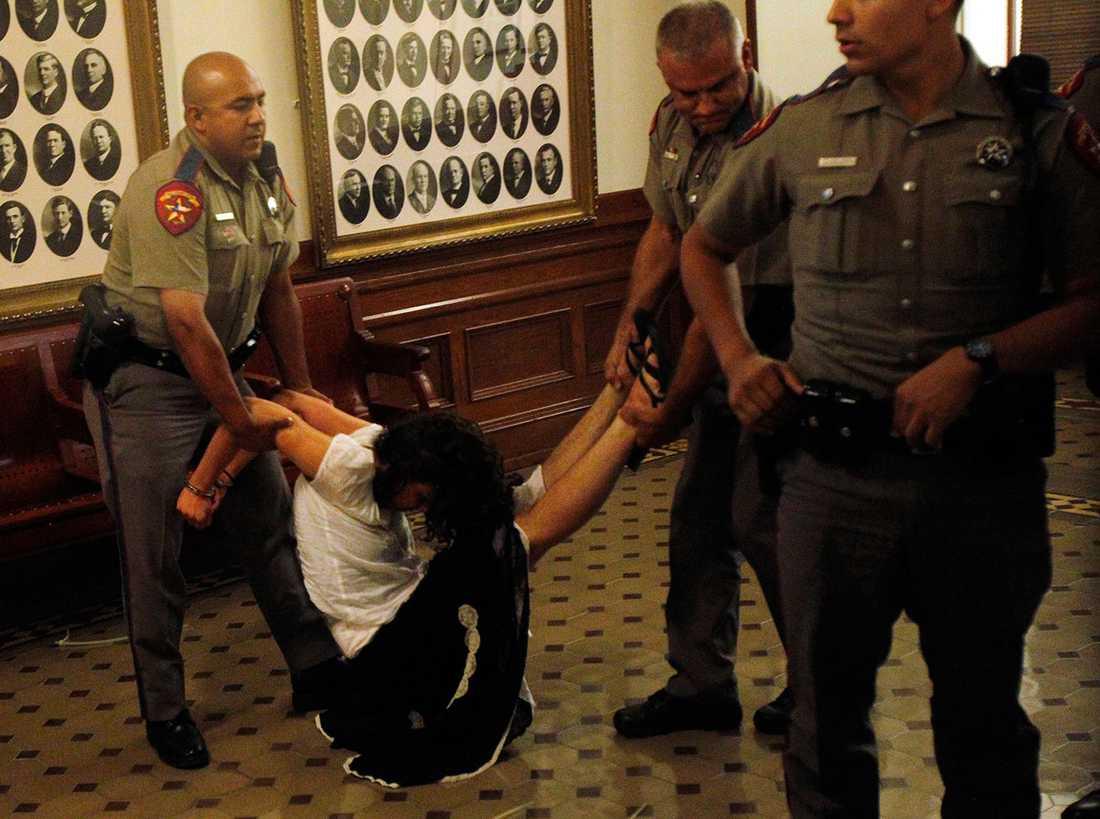 En kvinna som protesterar mot nya anti-abortlagen bärs bort av Texas state troopers.