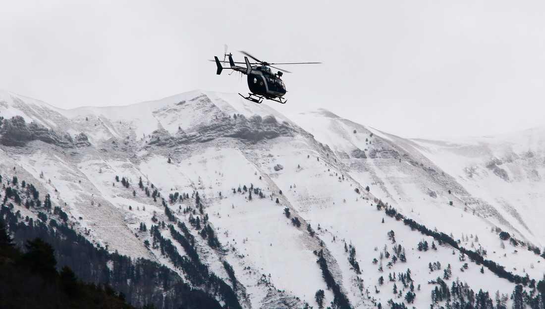 En fransk helikopter flyger i området kring platsen där planet kraschade.