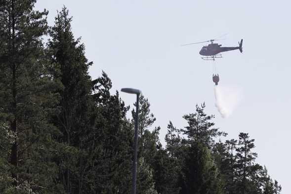 En helikopter vattenbombar branden under måndagseftermiddagen. Larmet kom strax efter klockan 14.