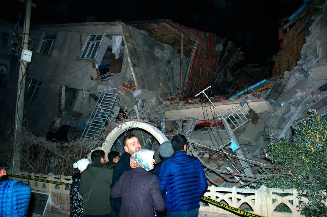 Människor framför en byggnad som rasat samman i staden Elazig i östra Turkiet. Minst fyra människor dog i en kraftig jordbävning.