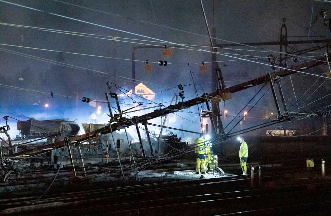 Under natten till torsdagen pågick arbete vid de kontaktledningar som fallit ner över spåren norr om stationen i Hässleholm i samband med en våldsam brand i en industribyggnad.
