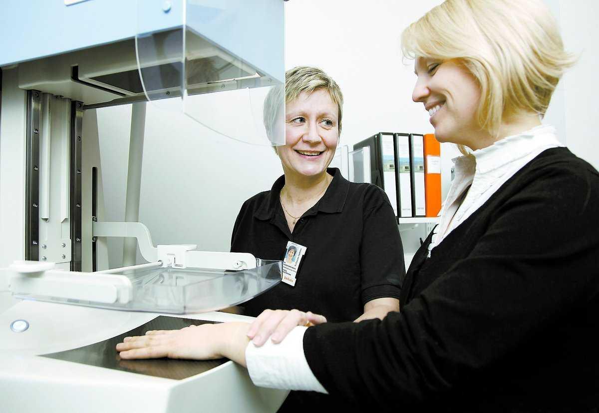 Sjuksköterskan Ann Eliasson Svensson hjälper Isabelle Mörling att ta en bild av handen. Analysen av bentätheten kommer direkt från en dator.