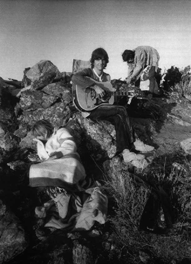 Gram Parsons spelar gitarr på klippa vid Joshua Tree. I bakgrunden Keith Richards.
