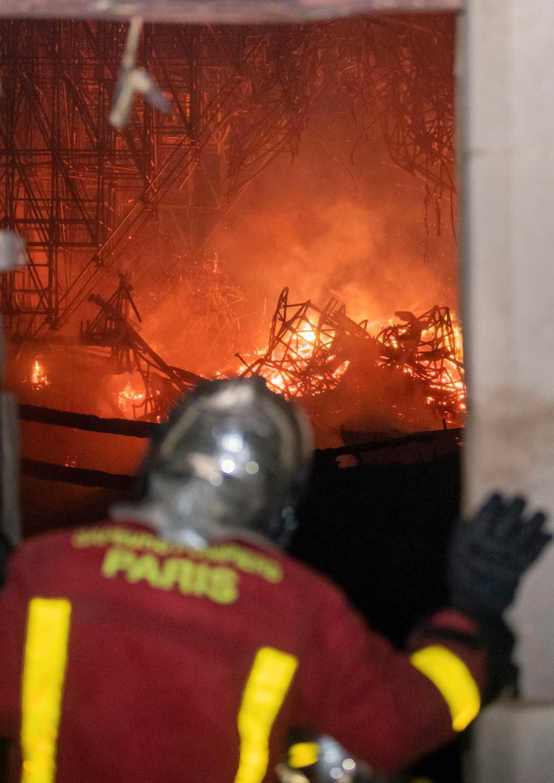 Person ur brandkåren tittar på branden i Notre-Dame.