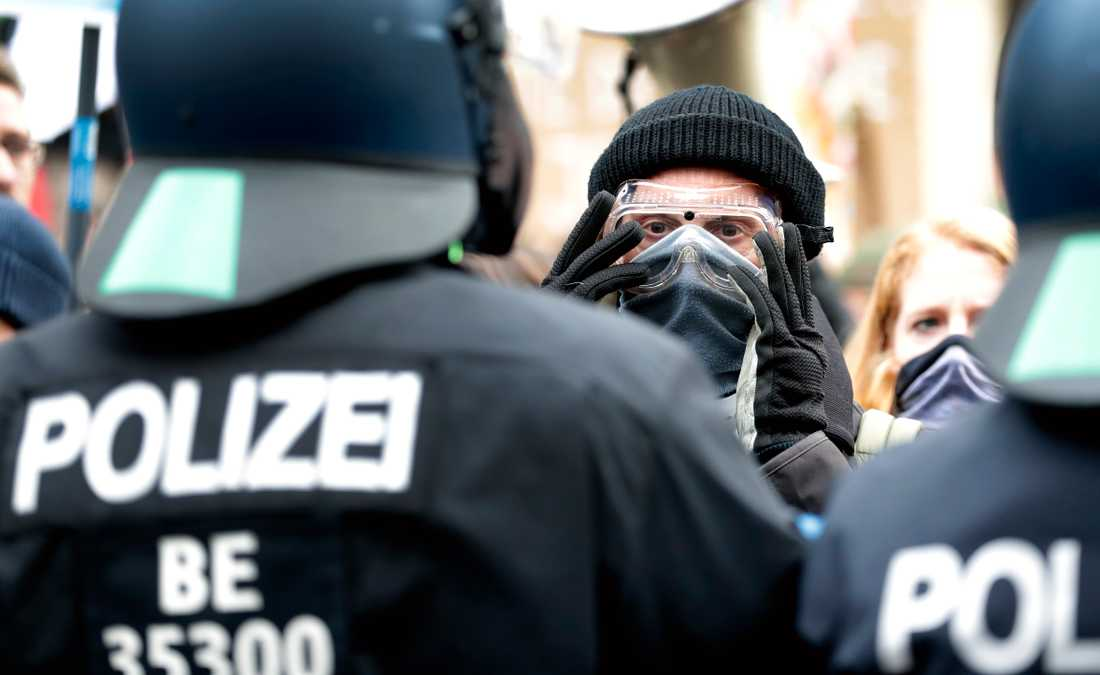 Myndigheternas restriktioner väcker ilskna reaktioner i Tyskland. Här står en demonstrant framför poliser vid en demonstration i Berlin förra veckan. Arkivbild.