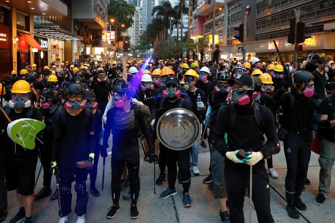 Aktivister i hjälmar och andningsskydd mot tårgasröken konfronterar polisen på en gata i Hongkong under söndagens protester.