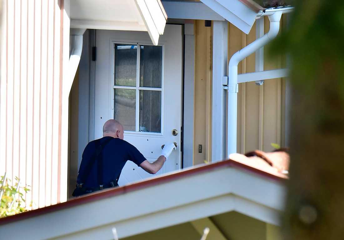 En polistekniker undersöker huset.