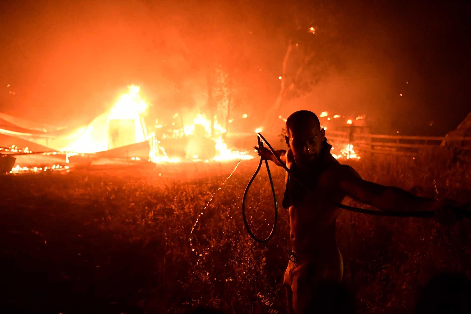 Un uomo spegne un incendio nel nord di Atene.
