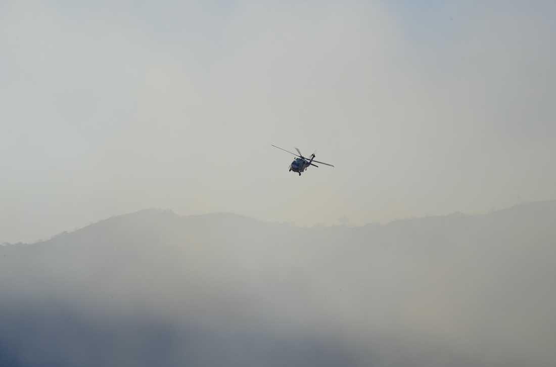 En räddningshelikopter flyger över bränderna.
