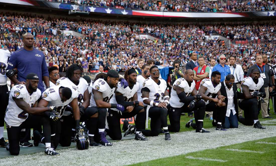 Spelare i Baltimore Raves står på knä under nationalsången.