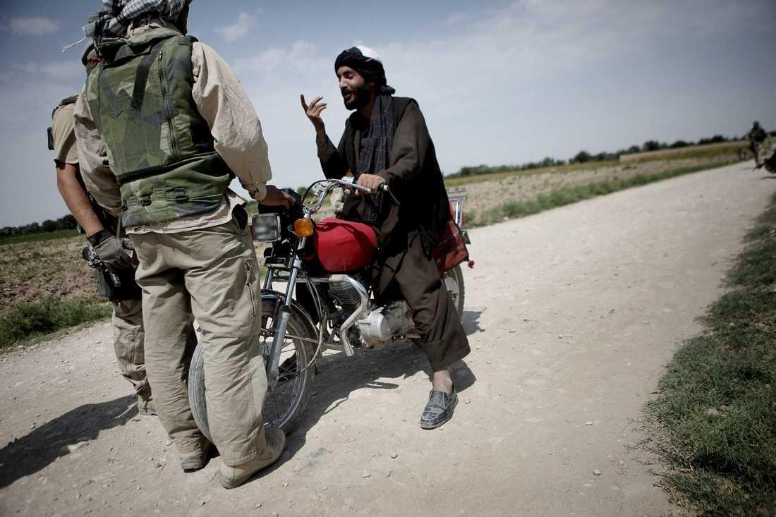 Soldaterna stoppar två misstänkta män på motorcykel i byn Alizayi för en kontroll.