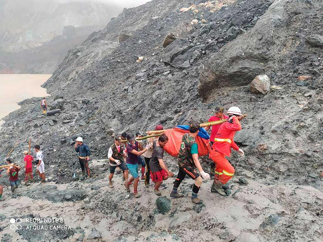 Räddningsarbetare bär en omkommen gruvarbetare efter jordskredet i delstaten Kachin.