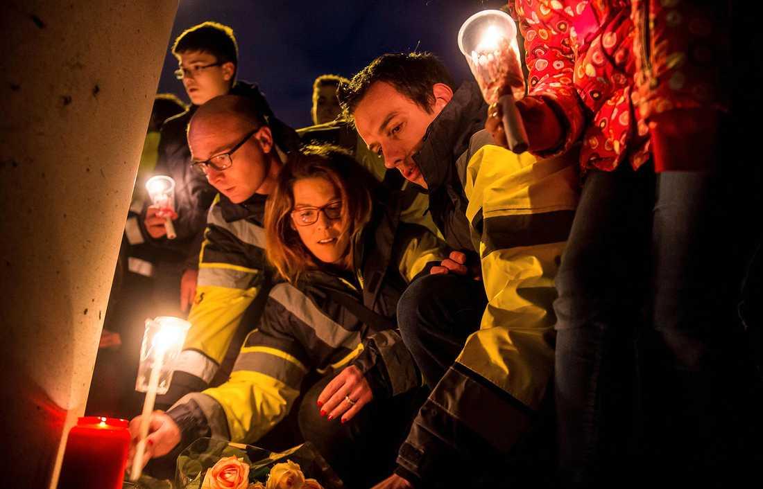 Flygplatsanställda tänder ljus för att hedra offren för terroratackerna vid en ceremoni nära flygplatsen Zeventem på onsdagskvällen.