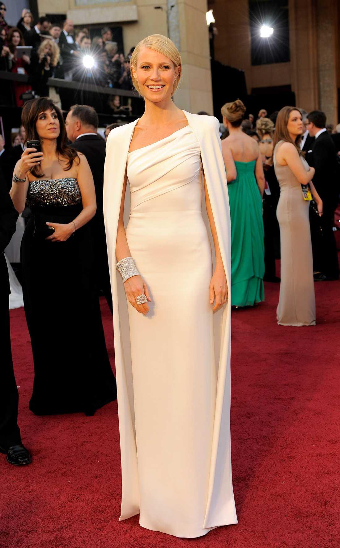"""Gwyneth Paltrow 2012 """"Ibland kommer det klänningar som sätter fingret på något och verkligen startar en trend. Så var falelt med den här krispigt vita och enkla looken komponerad Tom Ford. Gwyneth blev själva sinnebilden av den kommande trenden med raka linjer, ljusa toner och enkel elegans. Så snyggt!"""""""