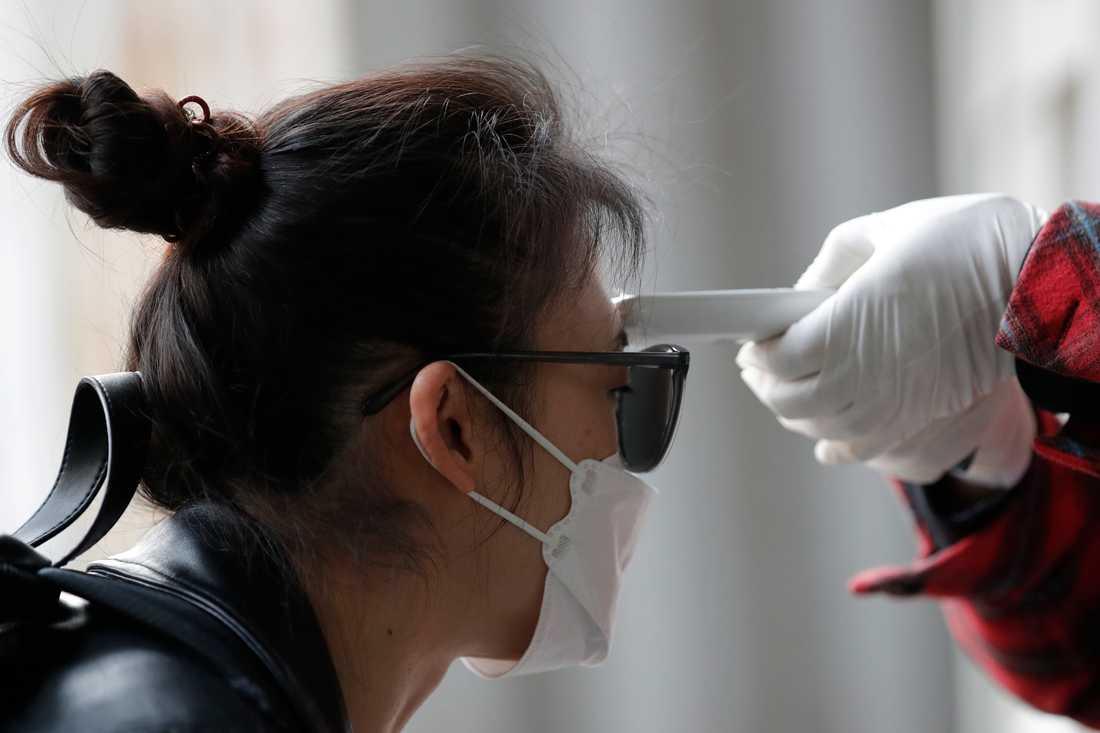 En väljare får kroppstemperaturen kontrollerad vid en vallokal i Seoul.