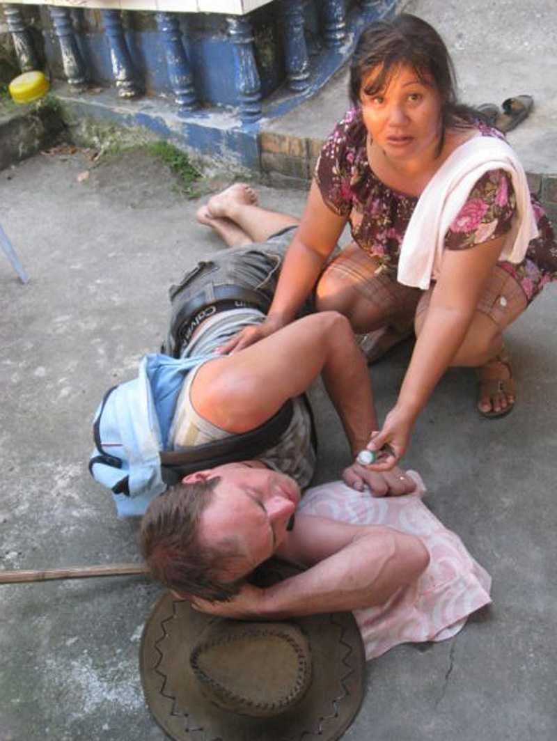 En thailändska ger första hjälpen till den skadade Gustav.