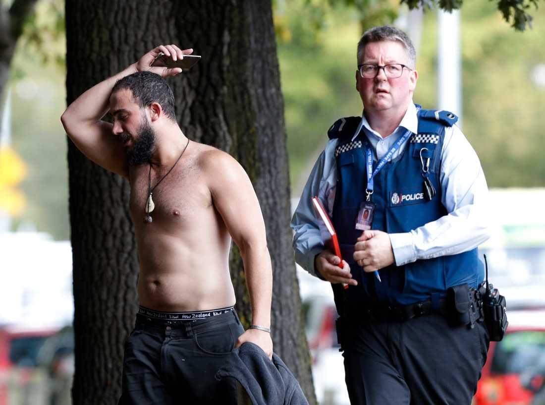 Polisen ser till så att en av männen som överlevde attentatet kommer bort från området närmast moskén.