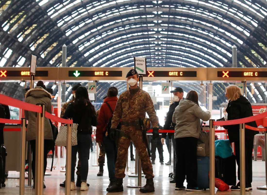 Poliser och soldater kontrollerar passagerare vid tågstationen i Milano.